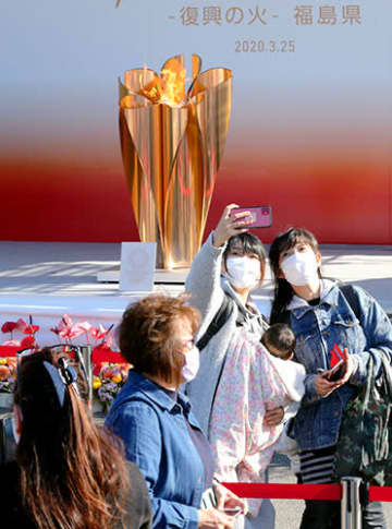 「復興の火」の前で記念撮影する親子ら=25日午後3時19分、福島県いわき市・アクアマリンパーク