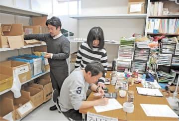 事務所内で食品を仕分ける職員とボランティア。経営難で4月から事業を縮小する