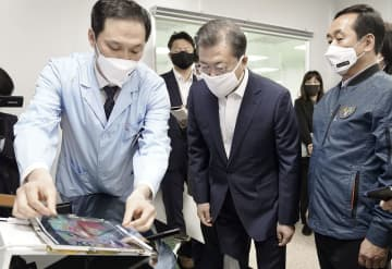 1日、半導体材料の製造工場を訪問し、説明を受ける韓国の文在寅大統領(手前中央)=韓国南東部・亀尾市(韓国大統領府提供・共同)