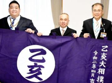 西日本豪雨で被災した乙亥会館に兵頭さん(中央)が寄贈した水引幕