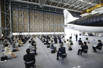 北九州空港にある航空機の格納庫内で開かれたスターフライヤーの入社式。新型コロナウイルスの感染拡大防止のため新入社員の全員がマスクをし、約2メートルの距離を取って並んだ=1日午後