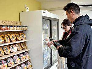 スマートフォンを使い買い物する利用客