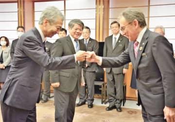玉城デニー知事(手前右)からグータッチの激励を受ける金城実政策参与ら=1日県庁