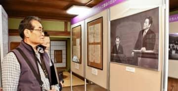 伊藤さんと古関さんが一緒に写った写真などに見入る来場者