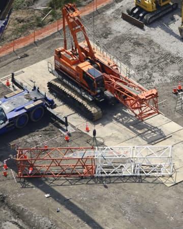 男性3人が落下したクレーンのアーム部分の下敷きになった熊本県宇土市の建設工事現場=2日午後1時40分(共同通信社ヘリから)