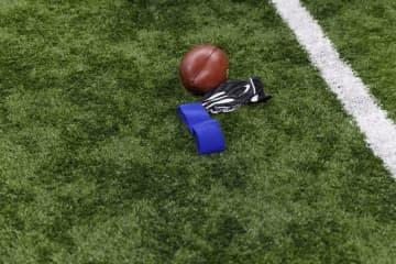 フィールドに置かれたフットボールとグローブ【Ryan Kang via AP】
