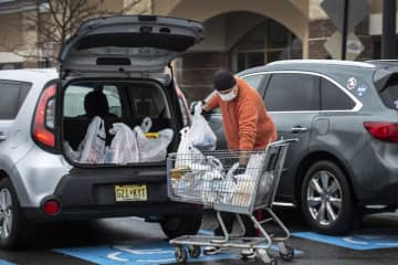 A shopper wearing a mask loads bags into a car in the parking lot of ShopRite of Lawrence. (Michael Mancuso   NJ Advance Media for NJ.com/)