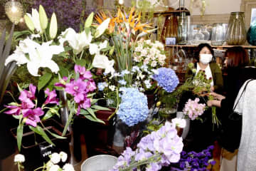 自宅用や家族へのプレゼントとしての花を求める女性客ら=3月31日、福井県福井市高柳1丁目の開花園本店