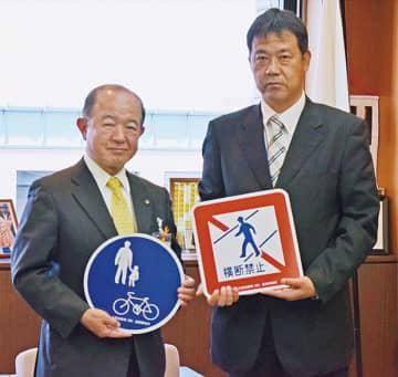 物品を寄贈した日産の磯貞之さん(右)
