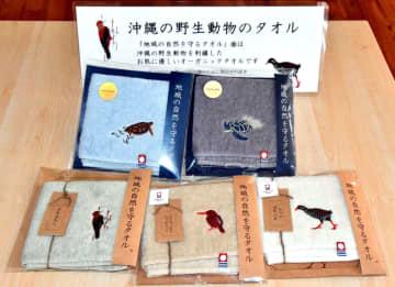 沖縄の野生動物の刺しゅうを施した「地域の自然を守るタオル」=3月20日、国頭村観光協会