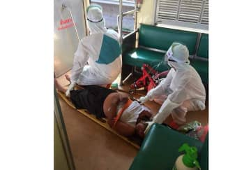 Health workers in protective gear prepare to remove a feverish woman from a passenger train for transport to hospital on Friday in Nakhon Ratchasima.