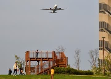 公園で親子連れが遊んでいる中、ごう音を立てて上空を飛ぶ旅客機=3日午後4時20分ごろ、川崎市川崎区の殿町第2公園