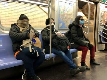 マフラーや服の襟元で顔を覆い隠す人も目立つ(ニューヨークの地下鉄で、筆者撮影)