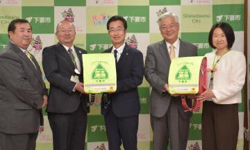 下妻市にランドセルカバーを寄贈したいばらきコープ生活協同組合の鶴長義二理事長(左から2人目)=同市役所