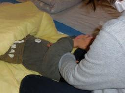 おなかに午睡チェックセンサーを付けて昼寝する園児=川西こども園(加古川市提供)