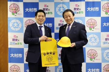 黄色い帽子とランドセルカバーを園田市長(左)に手渡す酒井会長=大村市役所