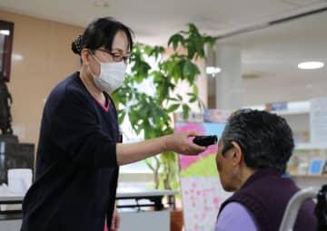 来院者の検温を行う病院スタッフ。海外渡航歴や症状も確認する=3日、国富町・けいめい記念病院