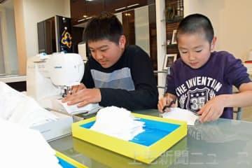 ミシンを上手に扱う小林さん(左)。弟の咲仁君も糸切りなどを手伝う