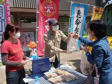 「イベントに出かけた気分だけでも味わって」と声を掛けながら、商品を手渡す泉さん(中央)と田中さん(左)=逗子市逗子