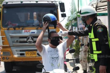 A police officer checks the temperature of a motorcyclist in Bangkok's Prawet district on Saturday. (Bangkok Post photo)