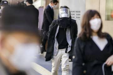 東京・新宿駅前を顔全体を覆うマスク姿で歩く人=6日午前10時17分