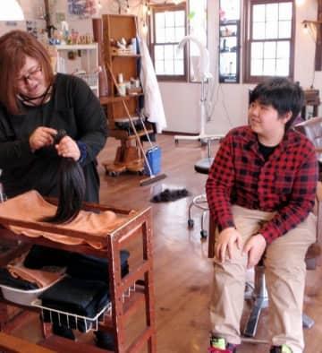 頭髪を失った子どもたちのために長年伸ばした髪を切った青山虎雅さん(右)と、寄付する髪を手にする母の由香里さん