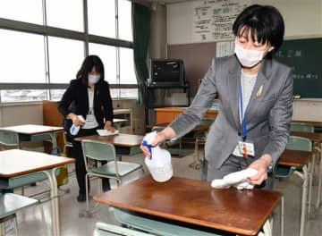 消毒スプレーを使い、教室の机や椅子を拭く教職員ら=6日正午ごろ、秋田市の大住小学校