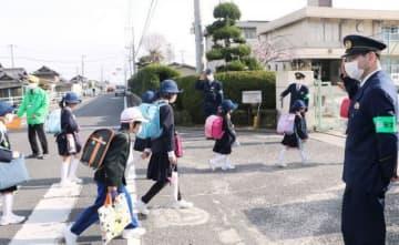第一藤田小校門前で児童を迎える岡山南署員ら