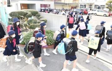 学校が再開され、マスク姿で久しぶりに登校する岡山市立幡多小の児童