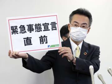 「緊急事態宣言直前」と書かれたボードを手に記者会見する福井県の杉本達治知事=7日午後、福井県庁