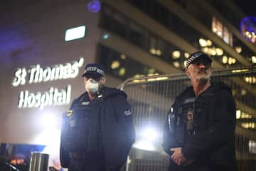 6日、英ロンドン中心部で、ジョンソン首相が入院する病院の外に立つ警察官(AP=共同)