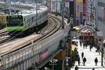 外出自粛要請で閑散とするアメ横商店街と、横を走るJR山手線=4日、東京・上野