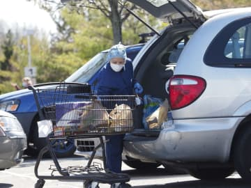 A woman loads groceries into her car at Wegmans in Woodbridge on Monday, Apr. 6, 2020. More people are wearing masks as the coronavirus speads throughout New Jersey.(Patti Sapone | NJ Advance Media                                /)
