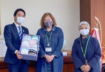 マスクを寄贈した同法人理事長の高井さん(中央)ら(市提供)