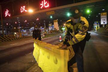 封鎖措置が解除され、中国・武漢の高速道路の料金所でバリケードを撤去する担当者=8日未明(新華社=共同)