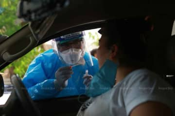 A medical official is collecting a sample from a taxi driver for a Covid-19 test in Samut Prakan province last week. (Photo: Somchai Poomlard)