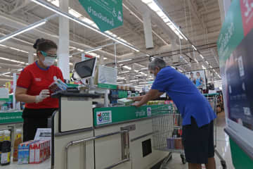 A cashier serves a customer at a hypermarket in Bangkok. Cashiers are under threat as it is an occupation that can be done by artificial intelligence and digital technologies. VARUTH HIRUNYATHEB