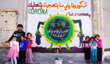Syrian artist Aziz Al-Asmar and children flash the victory gesture next to freshly drawn graffiti of a cartoon depiction of coronavirus, in Idlib province on March 23.