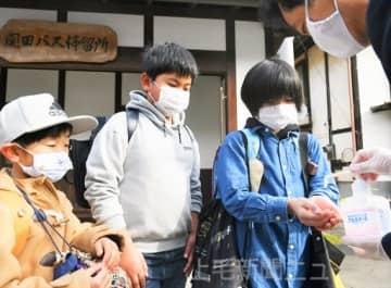 高山小では、児童がスクールバスに乗り込む際にアルコール消毒を行い、座席も離れて座るよう指示した=7日午前8時ごろ、高山村尻高