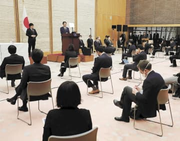 緊急事態宣言を発令し、記者会見する安倍首相(壇上)。記者の座席の間隔を空けて行われた=7日午後、首相官邸