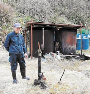 井戸(手前左)の状況を確認する石川さん。奥のタンクにたまった分はドラム缶に入れる