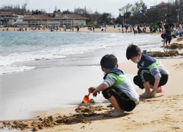 海岸で春の日差しを楽しむ子どもたち 山東省青島市