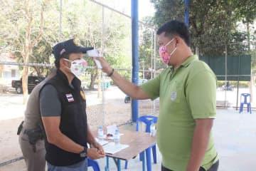 An official checks temperatures during Covid-19 surveillance in Phuket. (Photo: Achadtaya Chuenniran)