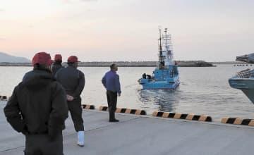 関係者に見守られて出港する小型捕鯨船=7日午前5時25分ごろ、石巻港