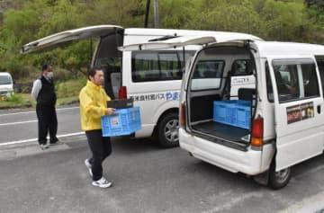 小川地区に到着した村営バス(奥)から荷物を運び出し、配達用の車両に移す村の委託配達員