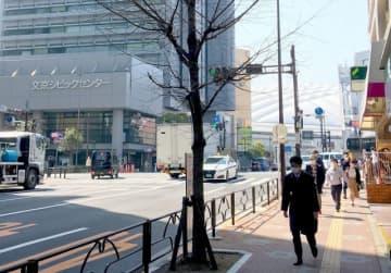 普段よりも人通りが減った文京区役所前の交差点。右奥は東京ドーム