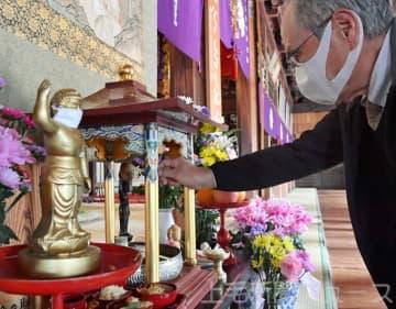 マスク姿の釈迦像に祈る檀家ら(アプリ「上毛新聞AR」をインストールしたスマホやタブレットをこの写真にかざすと動画を見ることができます)