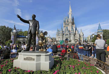 In this Jan. 9, 2019 photo, guests watch a show near a statue of Walt Disney and Micky Mouse in front of the Cinderella Castle at the Magic Kingdom at Walt Disney World in Lake Buena Vista, Fla. (AP Photo/John Raoux, File) (John Raoux/)
