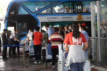 Twenty-six returnees from Japan go straight to a bus which will take them to a hotel in Bangkok for a 14-day quarantine. A total of 32 arrived from Haneda airport, but six did not pass screening and were sent to hospital.Varuth Hirunyatheb