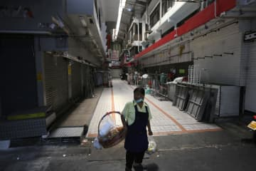 A woman looks on at a quiet market in Bangkok where all shops are closed. The government has come up with a 1.9-trillion-baht stimulus package to alleviate the economic impact of the Covid-19 outbreak.WICHAN CHAROENKIATPAKUL